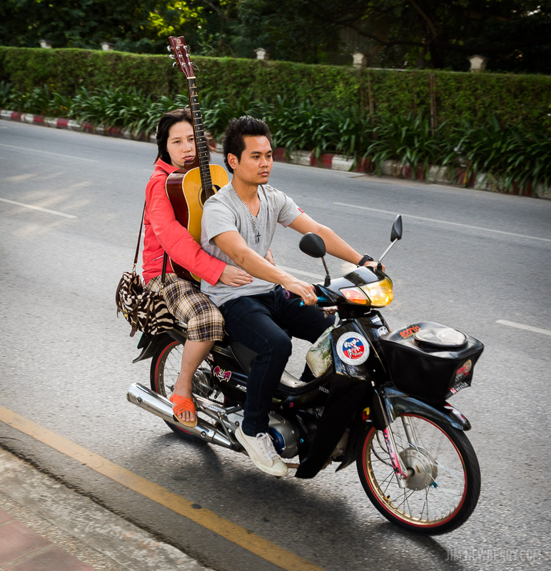 Woman holding acoustic guitar, riding on a scooter behind a man. Chiang Mai, Thailand. Photo by Jim Newberry.